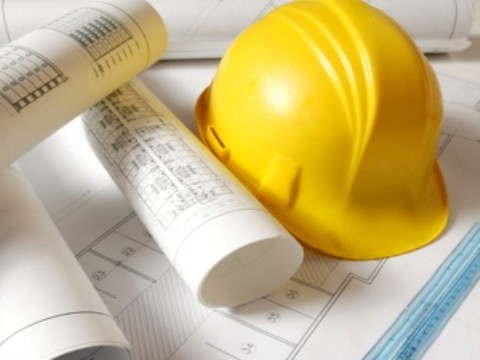 yelow hardhat on blueprints